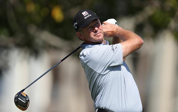 golfer in black hat swinging a golf club